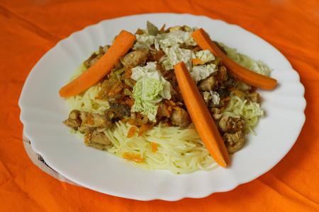 rýžové nudle drůbeží maso a zeleninu na bílém talíři s ohledem