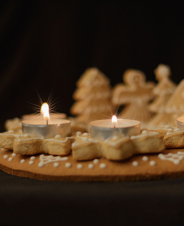 gingerbread wreath and lit candles on a dark background vertical view
