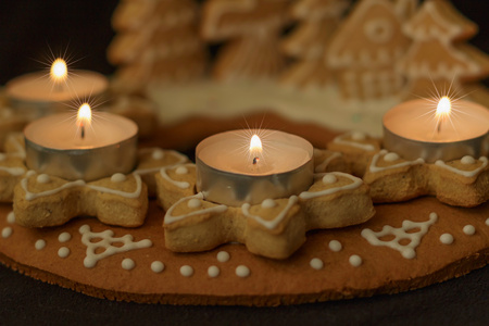gingerbread wreath and lit candles on a dark background