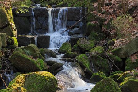 Vzdálený pohled na kaskádový horský potok mezi kameny