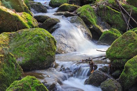 Proud tekoucí mezi záběrem kamene s hedvábným účinkem vody Reklamní fotografie