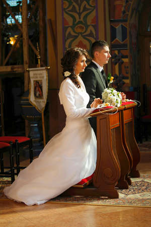 Bride and Groom in the church during wedding ceremony photo