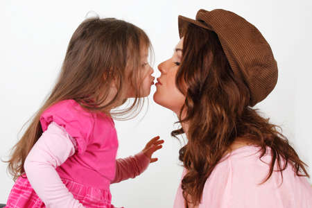Mother kissing her sweet dauther in the studio
