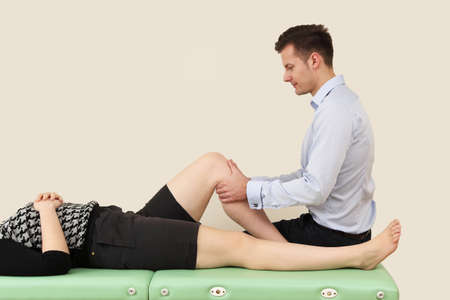 physical exercise: Young doctor rehabilitates his patient Stock Photo