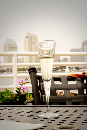 Glass of champagne with a city view - Stock photo