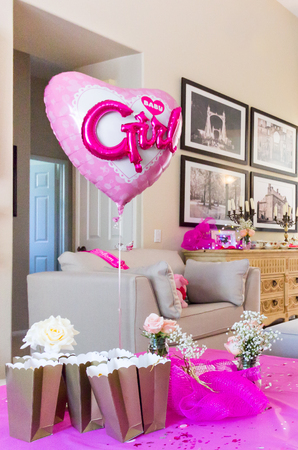 Large heart-shaped balloon with pink baby girl letters. Baby shower party decoration.