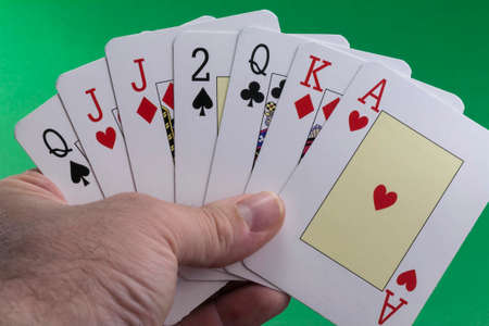 Hand holding a royal flush hearts on green photo