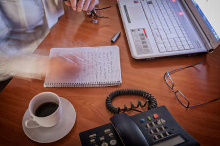 Close-up of female write notes in a notebook quickly in the notepad at office Imagens