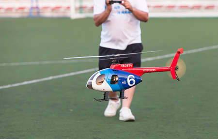heli: man piloting tiny radio controlled helicopter in the Football field, Spain Editorial