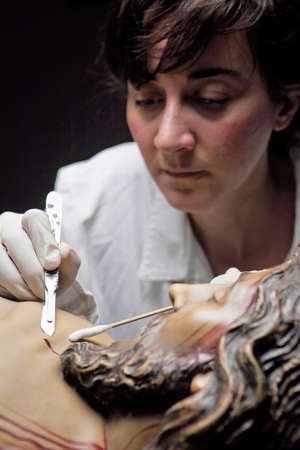restoring: conservative restoring an image of Christ crucified on wood, Andalusia, Spain