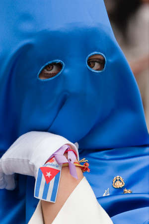 collectivity: Penitent with caperuz blue of penetrating look and nice eyes during a procession of Holy Week, Andalusia, Spain