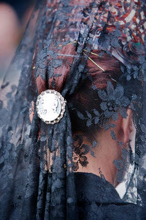 collectivity: Detail of mantilla and touched embroidered black with silver snap during a procession of holy week, Andalusia, Spain Stock Photo