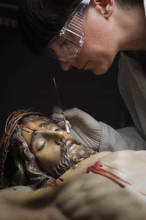 impregnated: Pulizia del viso di una scultura lignea del Cristo crocifisso con un isopo impregnato con dimetilformammide, Andalusia, Spagna