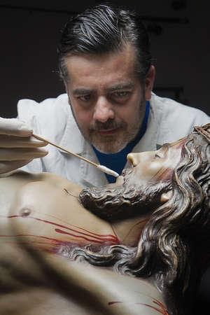 impregnated: Pulizia del viso di una scultura lignea del Cristo crocifisso con una isopo impregnato di dimetilformammide, Andalusia, Spagna