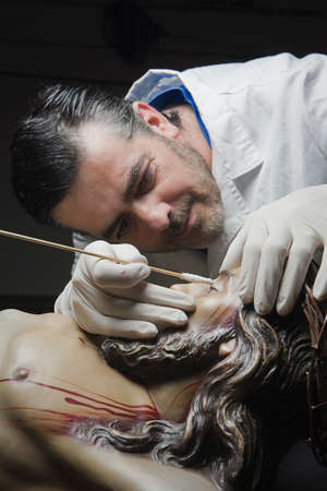 restoring: conservative restoring an image of Christ crucified on Carving wood, Andalusia, Spain