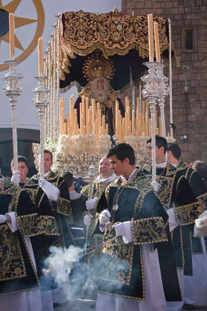 collectivity: Young people in procession with incense burners and processional candlesticks in Holy week, Linares, Jaen province, Spain
