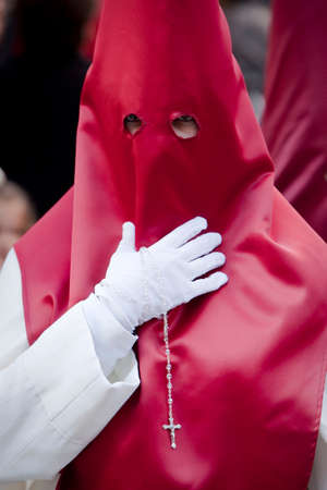 collectivity: Penitent with a rosary in his hand in a procession, Spain