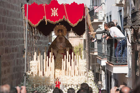 Women in a balcony by touching the embroidery of the throne of the virgin Mary during palm sunday, Linares Jaen province, Spain