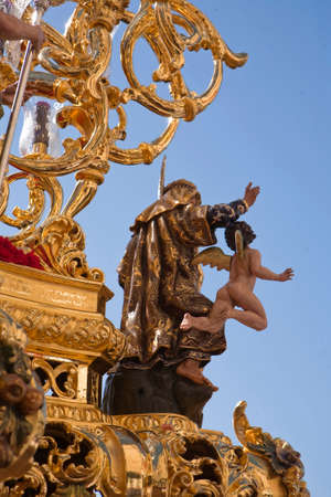 collectivity: Polychromed figure in a golden throne during a procession of holy week, Seville, Spain