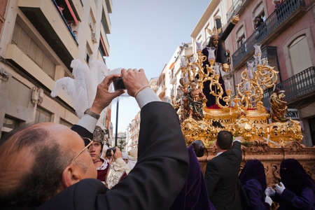 collectivity: Man taking photographs during a Holy week in the good Friday procession, brotherhood of El Nazareno, Linares, Ja�n province, Andalusia,  Editorial