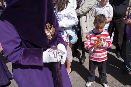 collectivity: Child with a toy trumpet during a procession of holy week, Spain