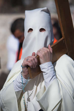 collectivity: Penitent carried a wooden cross in a procession of Holy week, Seville, Andalusia, Spain