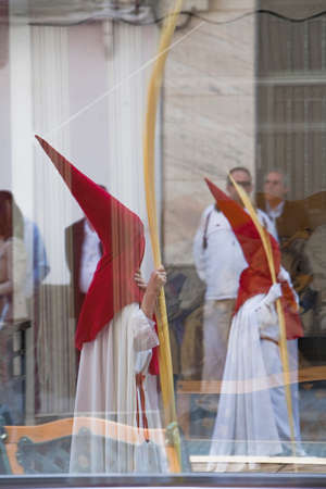 palm sunday: Two penitents reflected in a glass in a procession of holy week on Palm Sunday, Spain