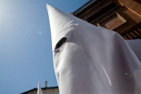 collectivity: Detail penitent white capirote during Holy Week , Spain Stock Photo