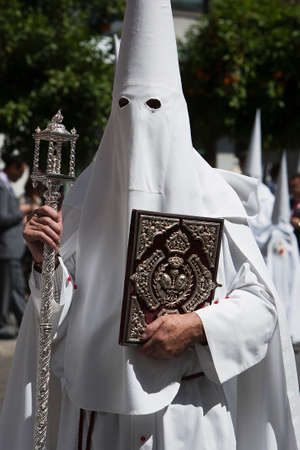 penitent with the rule book governing the brotherhood with velvet caps and appliques of embossed silver, Spain photo