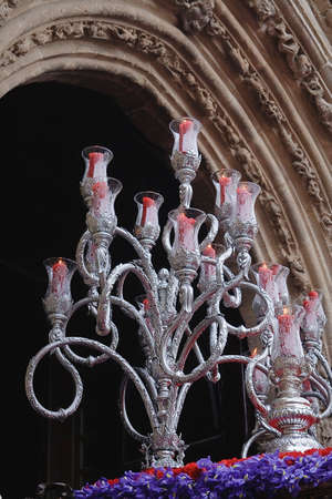 Silver chandelier with candles also called red chandelier of queue at the door of a church, Spain photo