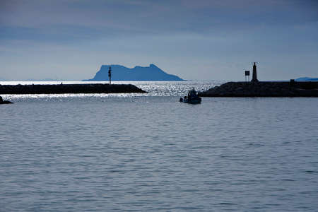 Fishing boat entering the port of Estepona, Gibraltar in the background, province of Malaga, Andalucia, Spain photo