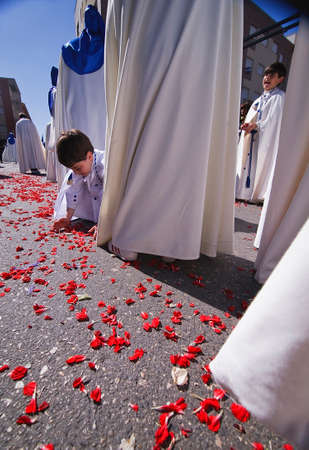 Child holding the ground rose petals during a Holy week procession, Spain