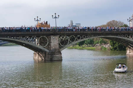 collectivity:  Brotherhood of San Gonzalo passing the holy Monday by the Puente de Triana, Seville, Spain