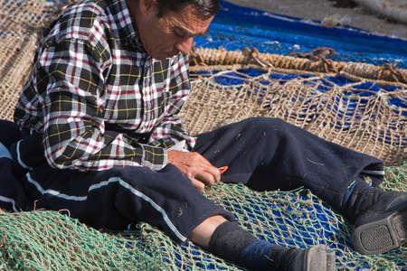 redes de pesca: Marinero fija sus redes de pesca en el puerto de Estepona, provincia de M�laga, Espa�a Editorial