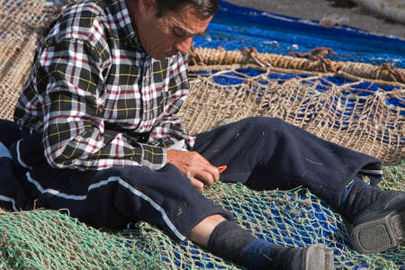 untangle: Sailor fixed their fishing nets in the port of Estepona, province of malaga, Spain