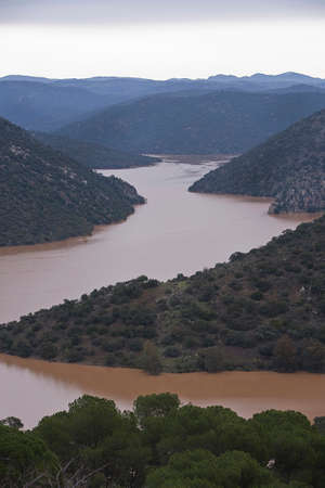 completely: The andula reservoir completely full of water in sierra morena, close to the dam of Jandula, Andujar, Jaen province, Spain