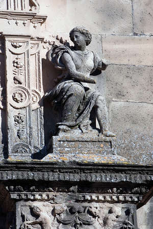 pilaster: Female figure sitting on a pilaster and arc with floral decoration in the main facade of the chapel of El Salvador, renaissance style, Ubeda,Jaen province, Spain Stock Photo