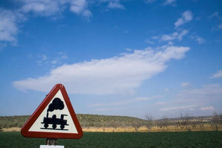 Warning sign worn of level crossing without barriers, blue sky with clouds photo