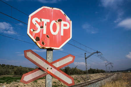 Warning sign worn of level crossing without barriers, blue\ sky with clouds