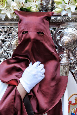 collectivity: Nazarene that goes with the hand on the manigueta the throne in a procession of holy week  Not wearing capirote, and the mask falls loose by the head, back, like the penitents, Spain
