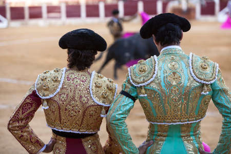 bullfighters:  Ubeda, Jaen province, SPAIN - 29 september 2010  Spanish Bullfighters looking bullfighting, the Bullfighter on the left dressed in suit of lights of colors red and gold and the right color pistachio and gold in Ubeda, Jaen provincia, Andalusia, Spain Editorial