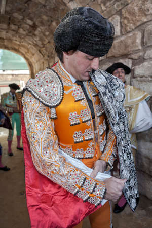 initiating: Ubeda, Jaen province, SPAIN - 29 sebtember 2010  Spainish bullfighter Jose Manuel Montoliu with orange dress and silver putting itself the walk cape before initiating the inaugural procession in the Bullring of Ubeda, Jaen province, Andalusia, Spain Editorial