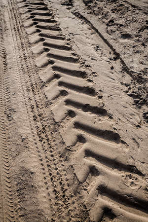 Tractor tire tracks on beach sand  Horizontal shot photo