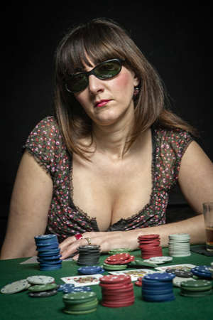 Attractive woman subject his sunglasses while playing a game of poker