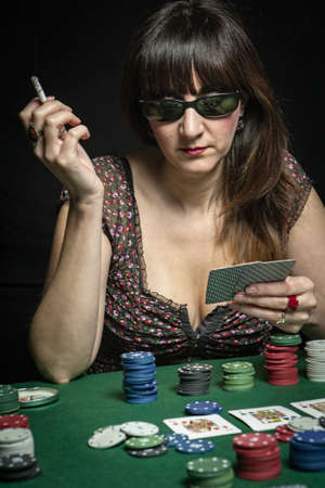 Sexy Woman with cigarette and sunglasses bet in a poker game photo