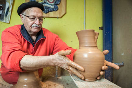 Potter by placing a piece of clay recently made on a wood table, clay pottery ceramics typical of Bailén, Jaen province, Andalucia, Spain Stock Photo - 25578725