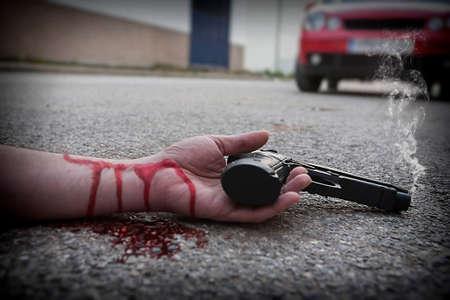 Man with gun in hand bloodstained lies dead in the asphalt murder victim Banco de Imagens