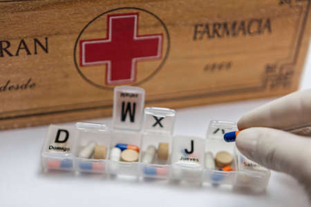 Pills with pill organizer next to old wood kit Banco de Imagens