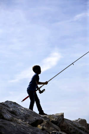 Silhouette of boy fishing in Estepona, Malaga province, Andalusia, Spain photo