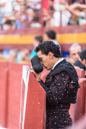 rite: Bullfighter with montera starting rite of praying before bullfight, Spain Editorial